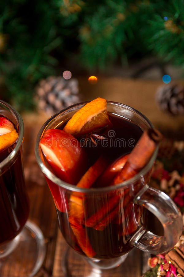 Close up of Christmas mulled wine with fruits and spices on wooden table. Xmas decorations in background. Winter warming drink fr. Close up of Christmas mulled stock photo