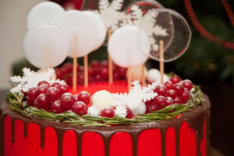 Close up Christmas red cake with chocolate smudges, decorated red currant, candy and lollipops and Christmas tree on the stock photos