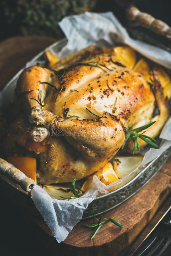 Close-up of Christmas roasted whole chicken with rosemary, bulgur, oranges royalty free stock photo