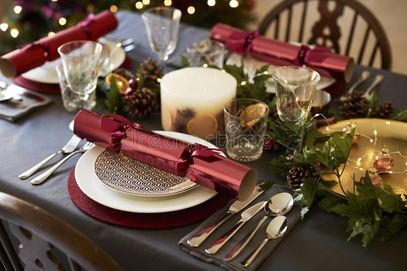 Close up of Christmas table setting with Christmas crackers arranged on plates and red and green table decorations, elevated view stock photo