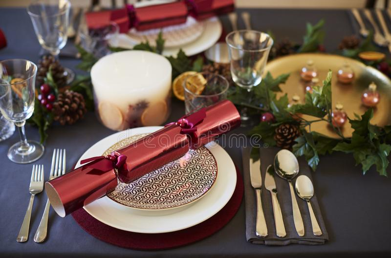 Close up of Christmas table setting with crackers arranged on plates and red and green table decorations, close up stock photo