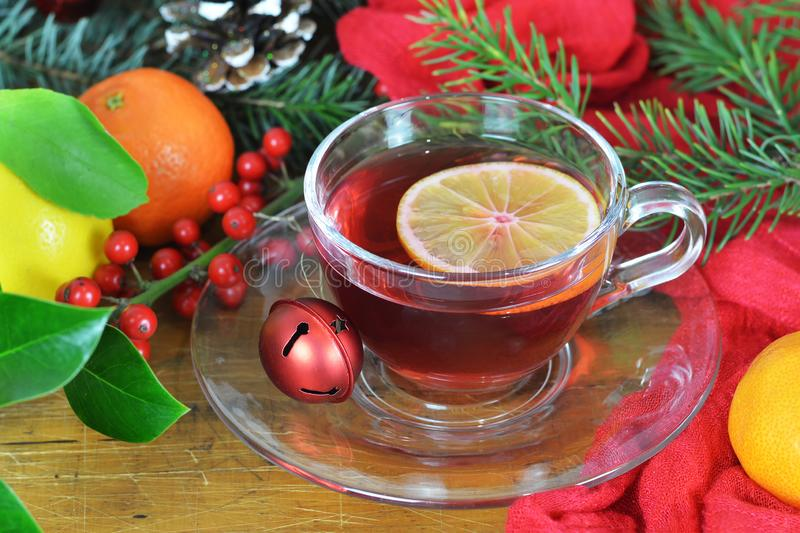 Christmas tea with lemon slice in transparent cup on wooden table stock image