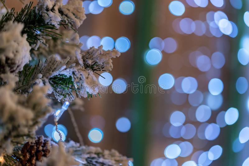 Christmas background of branches and blurred light. Close up Christmas tree branches with snow and blurred lights for festive background royalty free stock image