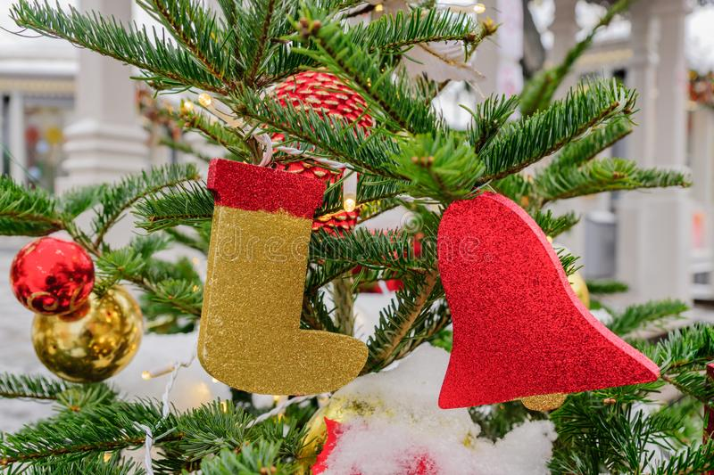 Close up of christmas tree decorated with balls, candy cane, bells and garlands. Festive street arrangement.  royalty free stock photography