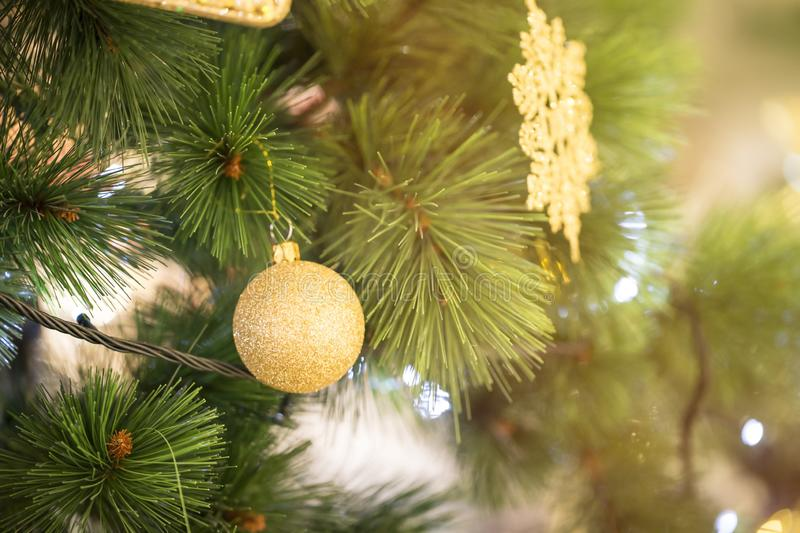 Close up of Christmas tree decorated with gold ball with boken b. Ackground royalty free stock images