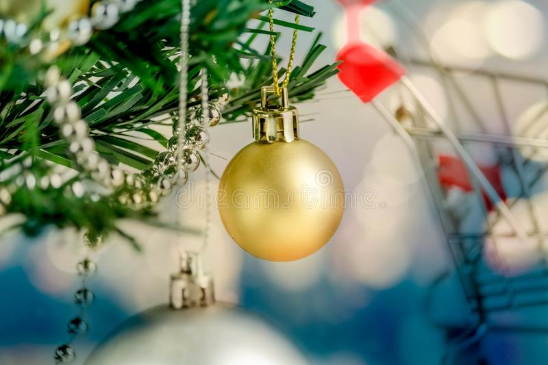 Close-up of Christmas tree is decorated with shopping cart for shopping and bokeh blue tone background, gold and silver balls on a stock photo