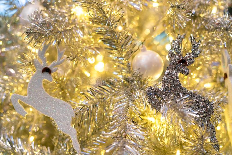 Close up Christmas tree decoration with white balls, silver reindeer and red bear and golden light. Xmas background. Christmas stock photo