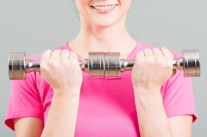 Close-up of chrome dumbbells in woman hands. For training and exercising in the gym royalty free stock image