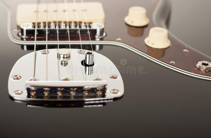 Close up of chrome tremolo tailpiece on black electric guitar, studio shoot. Red tortoise shell pickguard.  royalty free stock images