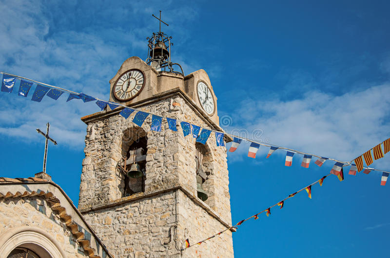 Close-up of church steeple on stone bricks at sunset, with clock and flags in Gréoux-les-Bains. royalty free stock photos