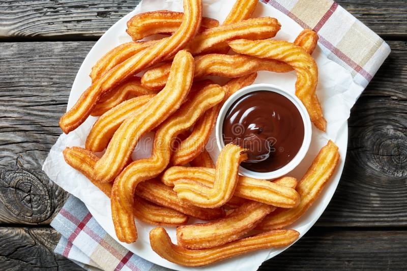 Close-up of churros on plate with chocolate sauce stock photos