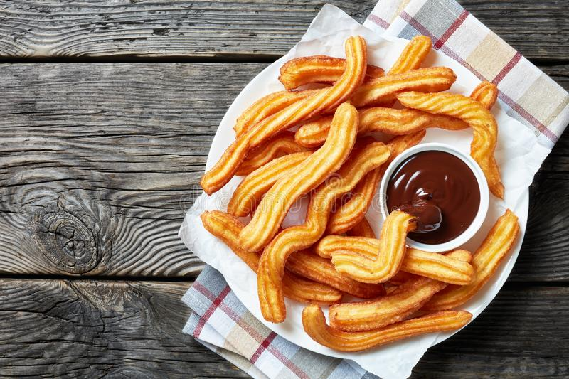 Close-up of churros on plate with chocolate sauce royalty free stock images