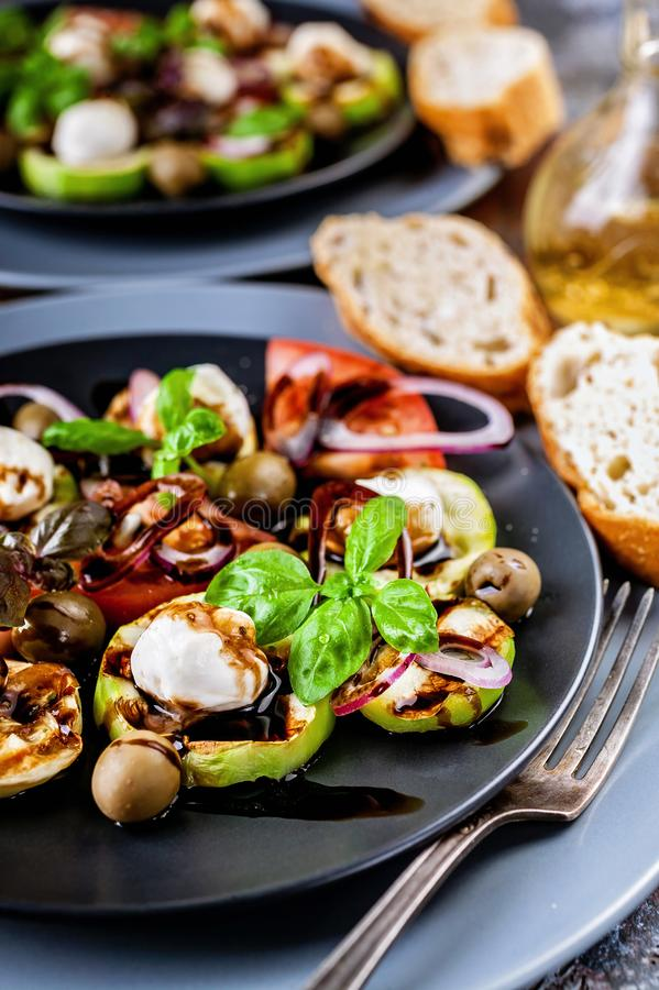 Close-up of ciabatta, Italian salad with grilled vegetables, basil and balsamic sauce on rust background. Mediterranean Kitchen. royalty free stock photos