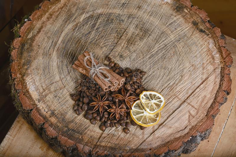 Close-up cinnamon sticks tied and dried lemon slices, anise star, scattered coffee beans, on wooden background, top view, place fo stock photos