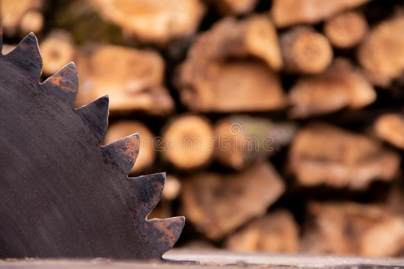 Close-up circular saw and firewood on background. The circular saw and harvest firewood for the winter on background royalty free stock photography