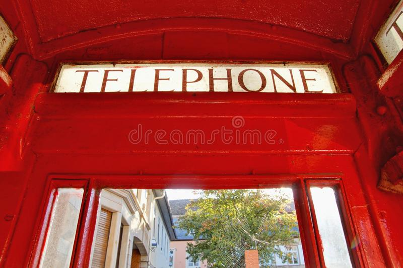 Close up of Classic English London Phone Booth, Red cabin with windows. The word Telephone is written on the red phone box. A red phone box, view of the Classic stock image