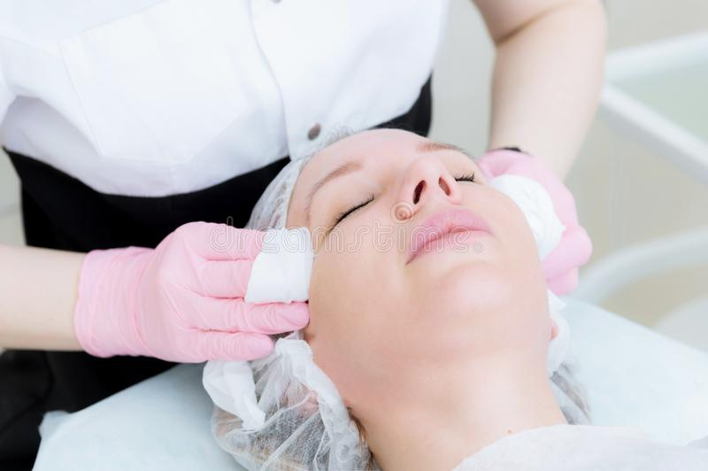 A close-up of the cleaning procedure in the office of cosmetology. The hands of the cosmetologist in pink gloves are royalty free stock photo
