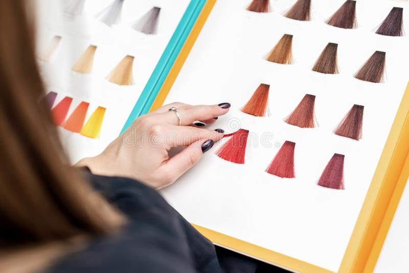 Close up of client`s hand choosing color from hair samples in salon stock images