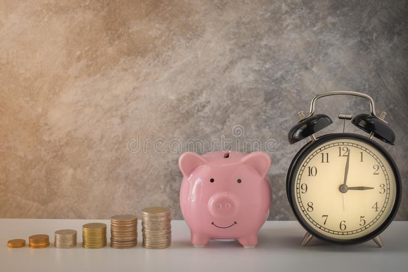 Close-up of clock and pink piggy bank smile with coins stack stair step up growing growth saving money. concept Business Finance, royalty free stock photo