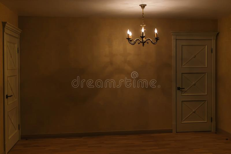 Close up of closed wooden door in the empty room with copy space. dark room with a door and a lamp royalty free stock photo