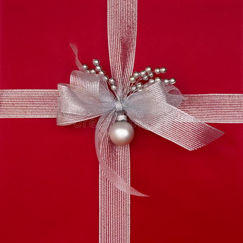 Close-up closeup of red Christmas gift present with metalllic silver ribbon, bow and decorations. Beautiful, fancy, elegant stock images