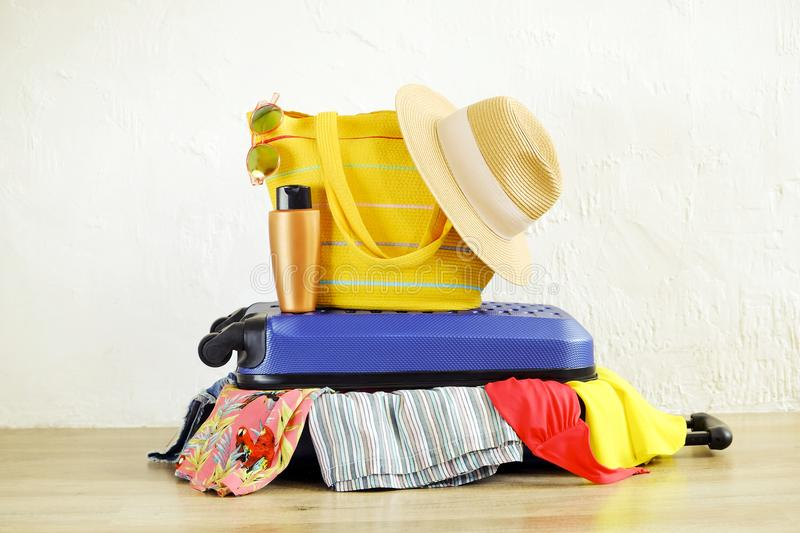 Close up of clothes don`t fit in messy fully packed closed suitcase, things sticking out. Blue hard shell luggage. Beach bag, hat. Sunglasses. Woman packing royalty free stock images