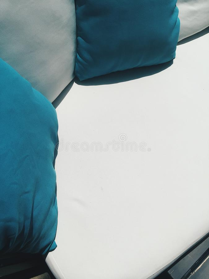 Close up coach with blue and white pillows outside at cafe terrace at sunny day.  royalty free stock photos