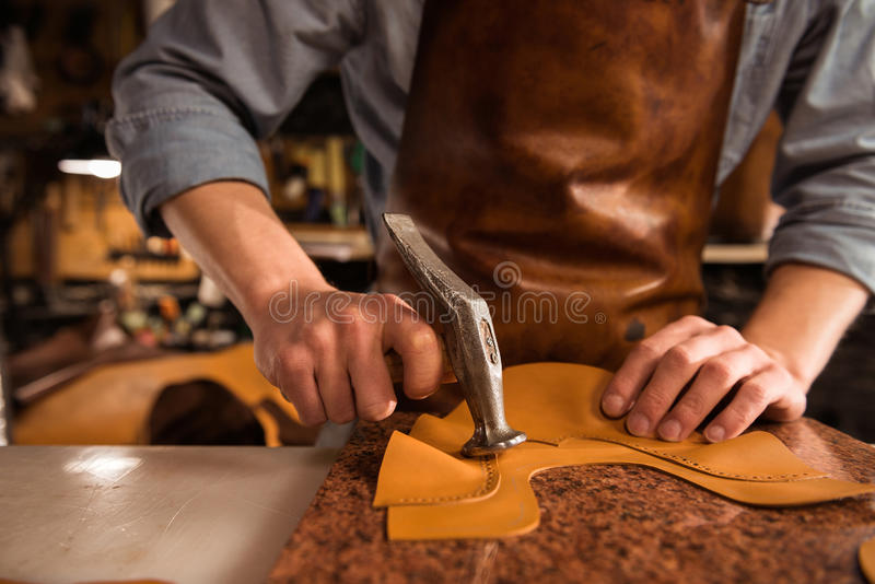 Close up of a cobbler working with leather. Textile and hammer at a workshop royalty free stock photos