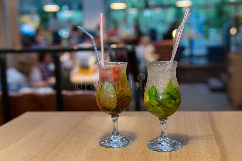 Close up cocktail with ice in glass and straw. Fresh cold mojito cocktail on a wooden table royalty free stock images