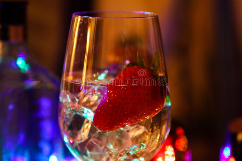Close up of cocktail with strawberry and ice cubes stock images