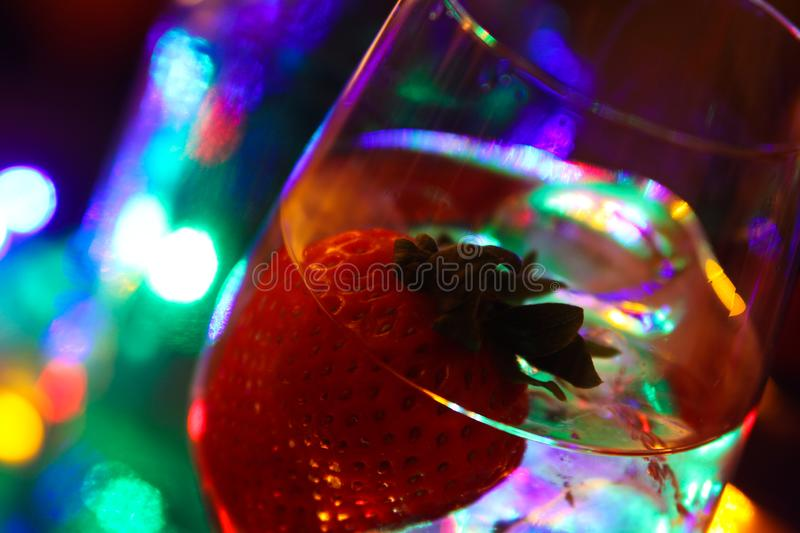 Close up of cocktail with strawberry and ice cubes royalty free stock image
