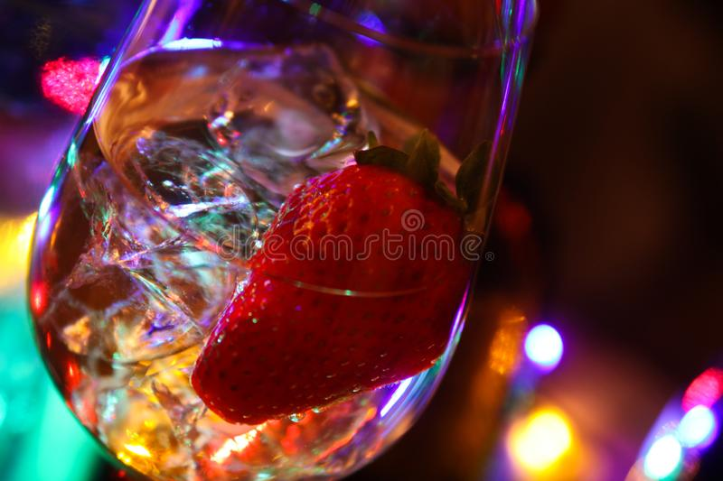 Close up of cocktail with strawberry and ice cubes. And colorful bokeh stock photo