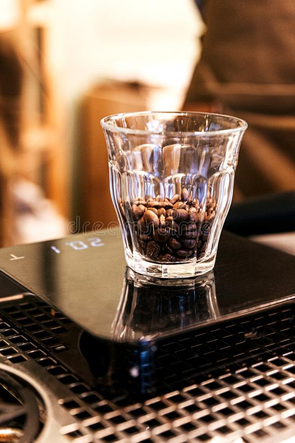 Close-up Coffee beans inside the shot glass on the digital weight scale stock photo