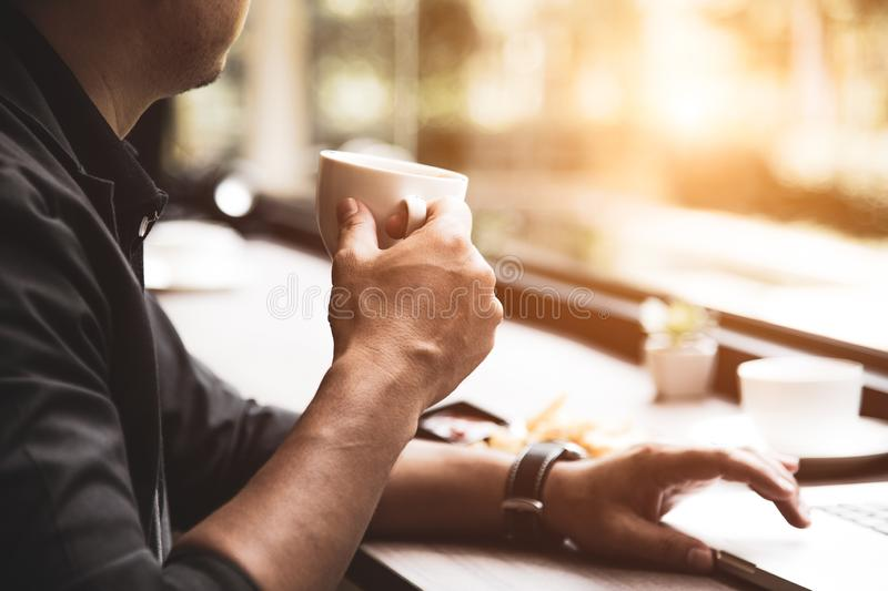 Close up of coffee cup on businessman hand. Man working with laptop computer. Business and Technology concept. Workaholics and royalty free stock photo