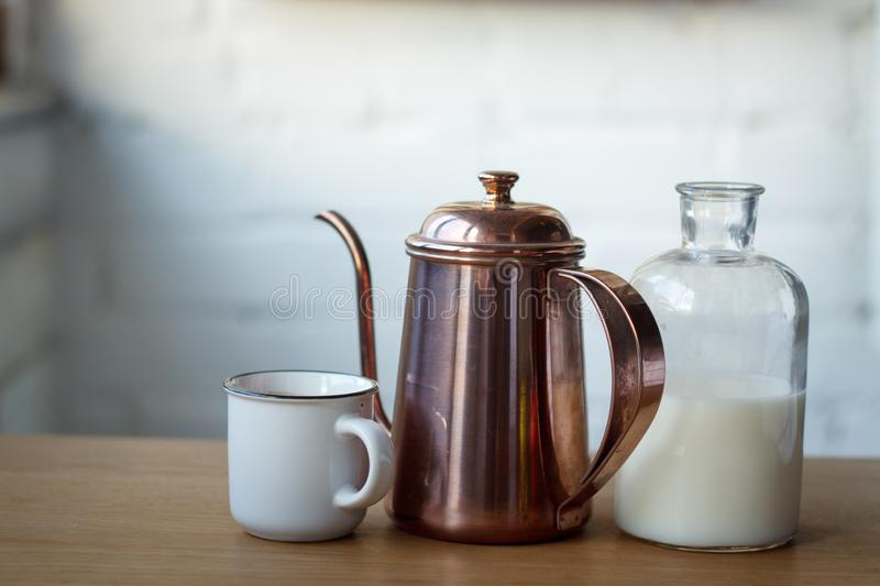 Close-up coffee cup, copper coffee pot and a bottle with milk on a light wooden surface, selective focus stock photography