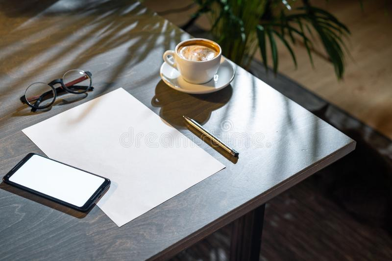 Close up of coffee cup ,glasses, paper, pen and mobile phone with blank screen. stock image