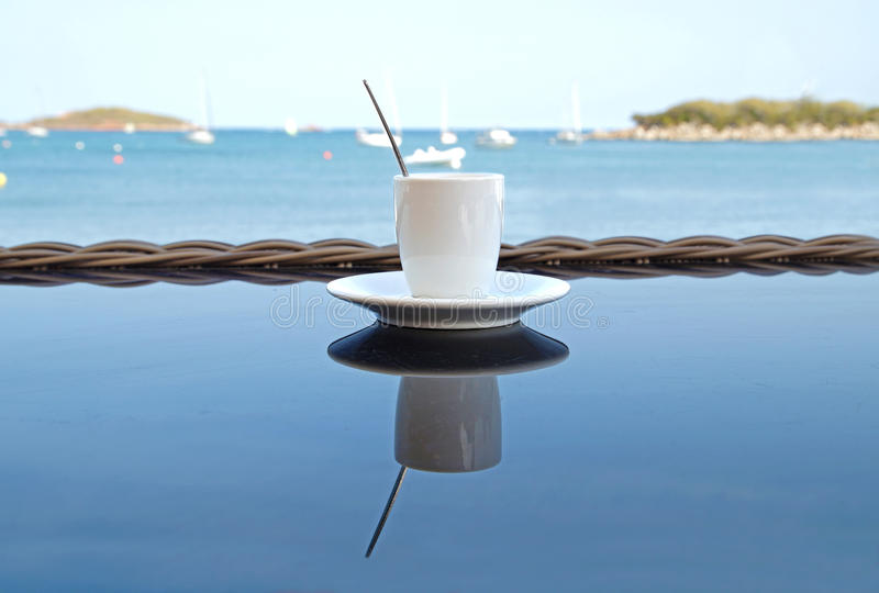Close up Coffee cup on wood table . View of tropical beach royalty free stock images