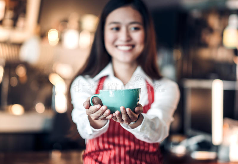 Close up on coffee up with blur asian woman barista holding mug stock photos