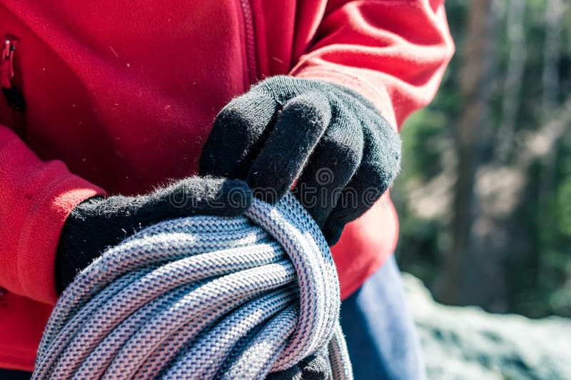 Close-up of a coiled blue climbing rope in the hands of a climber male stock photos