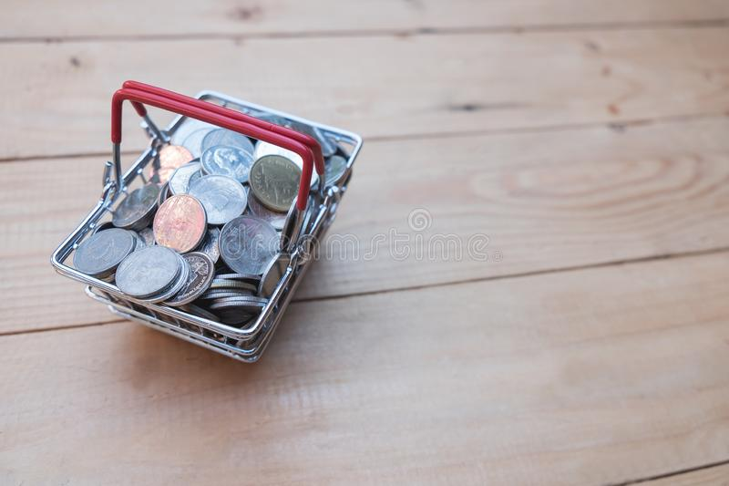 Close up coin in basket on wooden table of brown. Saving money concept stock photography