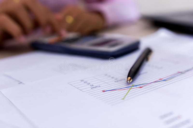 Close up Coin and pen on summary report and calculator on table. stock photos