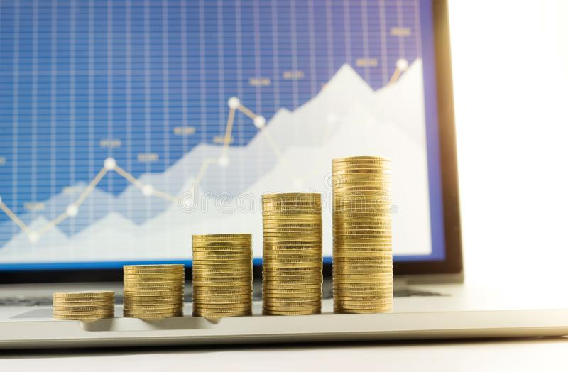 Close up coin stacked growing on financial graph chart in laptop. Screen background.For business growth and financial concept royalty free stock photo