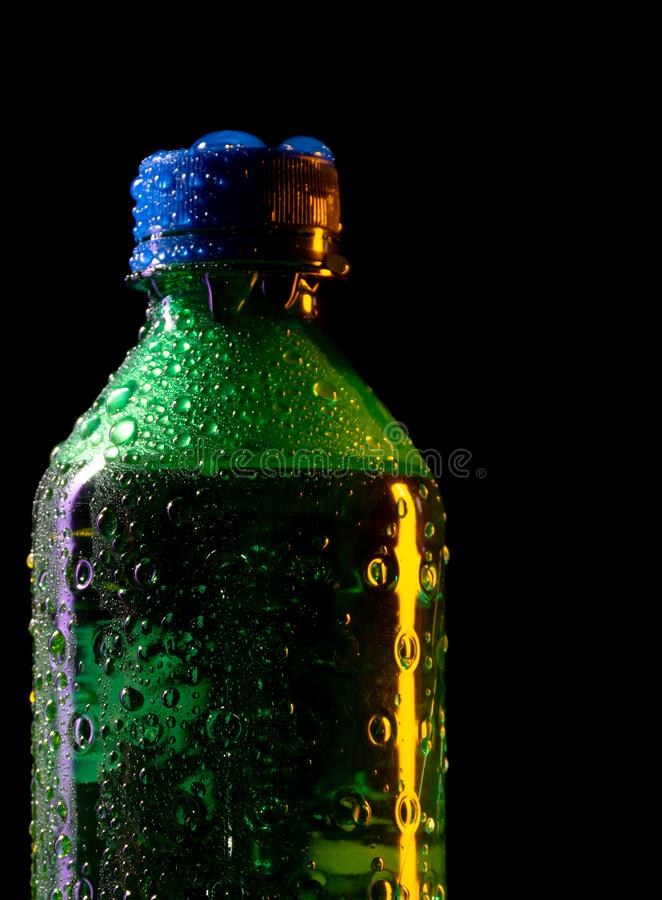 Close up of cold green plastic bottle with texture of water drops and frost isolated on black background royalty free stock photos