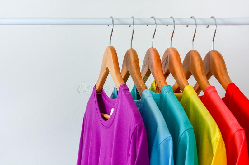 Collection of colorful rainbow t-shirts hanging on wooden clothes hanger in closet rack over white background stock images