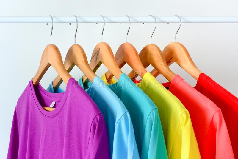 Collection of colorful rainbow t-shirts hanging on wooden clothes hanger on clothing rack over white background stock photography