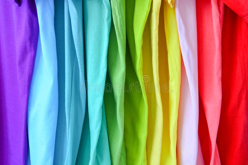 Collection of colorful rainbow t-shirts hanging on clothes hanger in closet royalty free stock photo
