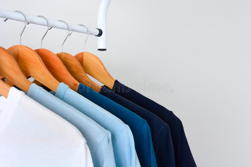 Collection shade of blue tone color t-shirts hanging on wooden clothes hanger in closet royalty free stock images