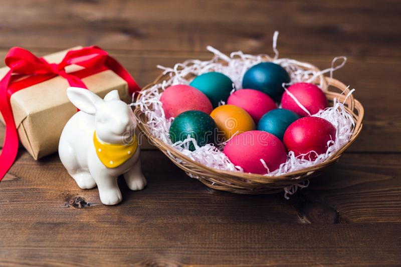 Close up of colored eggs in wicker basket , gift and bunny over wooden background royalty free stock photography