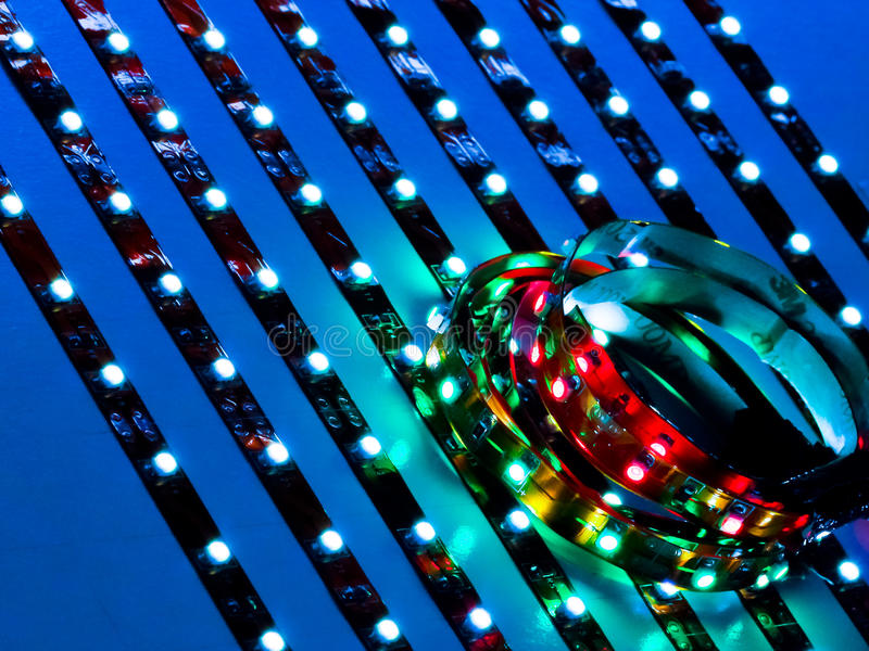 Close up of colored and white LEDs. Close up of colored and white LED lighting strips illuminated against blue background with very narrow depth of field stock photo
