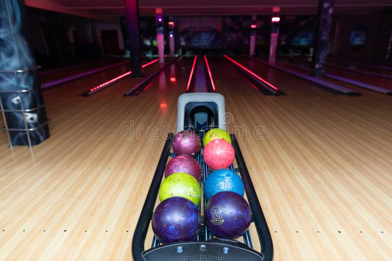 Close - up of colorful bowling balls. Bowling alley was laid in a wooden lane in the bowling hall. Colorful bowling balls in return machine. Multicolored bowling royalty free stock photo